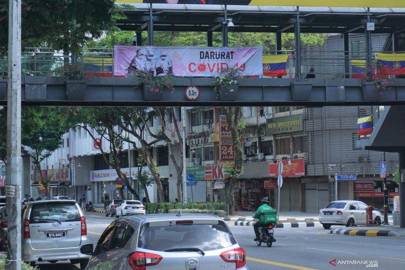 Pengendara lalu lintas melintasi spanduk bertuliskan darurat COVID-19 yang dipasang pada sebuah jembatan penyeberangan di Jalan Raja Laut Kuala Lumpur, Sabtu (13/2/2021). Foto : Agus Setiawan/Antara