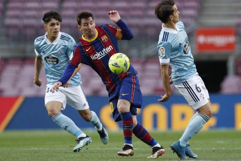 Lionel Messi berusaha untuk melewati dua pemain Celta Vigo dalam pertandingan Liga Spanyol di Camp Nou, Barcelona, Spanyol pada Minggu (16/5/2021). Foto : REUTERS