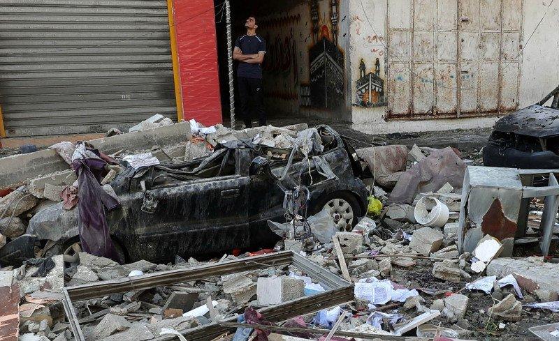 Seorang warga Palestina berdiri tak jauh dari puing reruntuhan yang diakibatkan serangan udara Israel di Jalur Gaza, Palestina Rabu (19/5/2021). Foto : Reuters.