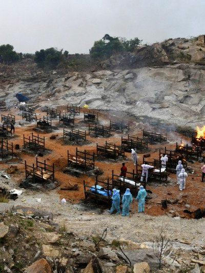 Relawan dan kerabat bersiap untuk mengkremasi jenazah orang yang meninggal akibat penyakit virus corona (COVID-19), di tempat krematorium di desa Giddenahalli di pinggiran Bengaluru, India, Minggu (2/5/2021). Foto : Reuters.