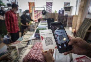 Pengunjung memindai kode QRIS untuk pembayaran dalam acara Karya Kreatif Indonesia (KKI) 2021 Eksotisme Lombok di kawasan Destinasi Pariwisata Super Prioritas (DPSP) The Mandalika, Praya, Lombok Tengah, NTB, Rabu (3/3/2021). Foto : Antara.